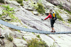 Woman trekking with backpack crossing bridge Royalty Free Stock Photography
