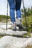 Woman with trekking boots and sticks on the rocky trail Stock Photography