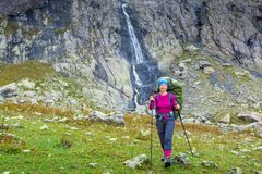 Woman trekking in Caucasus mountains against high waterfal in Us Stock Images