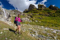 Woman trekking in Caucasus mountains against high waterfal in Us. Hba region Royalty Free Stock Photography