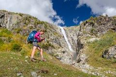 Woman trekking in Caucasus mountains against high waterfal in Us. Hba region Stock Image