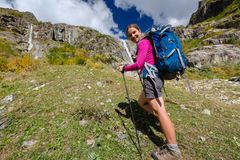 Woman trekking in Caucasus mountains against high waterfal in Us. Hba region Royalty Free Stock Photo