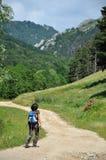 Woman trekking on a winding dirt lane, road ascending a mountain Stock Photos