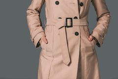 Woman in trench coat. Cropped shot of woman in trench coat on grey stock photography