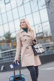 Woman in trench coat with luggage Stock Photo