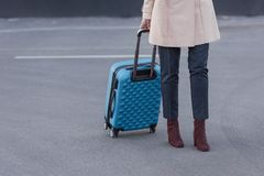 Woman in trench coat with suitcase Stock Photography