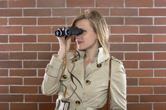Woman in a trenchcoat with binoculars. Young woman in a trenchcoat with binoculars Stock Photo