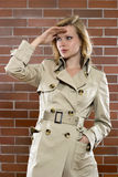 Woman in a trenchcoat on a lookout Stock Images