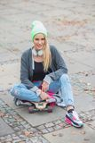 Woman in Trendy Attire Sitting Over Skateboard Stock Photo