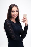 Woman in trendy black dress using smartphone Stock Photography