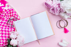 Woman Trendy Fashion Accessories. Such as Pink Court Shoes, Silk Pink Scarf, Bracelets, Notebook for writing Dreams and Flowers on Pink Background, Flat Lay Royalty Free Stock Photos