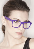 Woman with trendy glasses. Portrait of beautiful young woman wearing fashionable glasses with purple frames, studio background Royalty Free Stock Image
