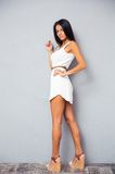 Woman in trendy white dress posing at studio Royalty Free Stock Photography