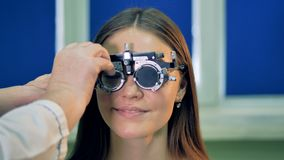 A woman in trial frame nods after test lenses are inserted. A woman sits for an eyesight test where a trial frame and test lenses are used stock footage