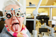 Woman with trial frame sticking out. Elderly woman with a trial frame sticking out tongue at the optician Royalty Free Stock Image