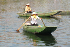 Woman in triangular hat in a paddle boat in Vietnam Royalty Free Stock Photos