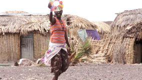Woman of the tribe elmolo goes between huts stock video