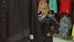 A woman tries on a leather coat in the store. Shop. Girl trying on a leather jacket in the store in front of the mirror. Shopping stock footage