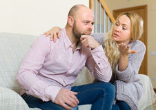 Woman tries reconcile with man. Woman asking for forgiveness from men after quarrel at home. Focus on guy stock photos