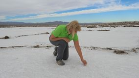 Woman Tries Salt To Taste Sitting On A White Surface Of A Dry Lake In The Desert. An adult active woman tries salt to taste frowns. Sitting on the white surface Stock Photo