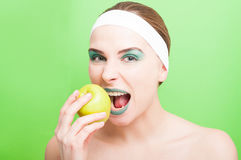 Woman tries to bite a fresh apple stock photography