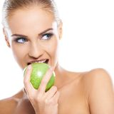 Woman tries to bite a fresh green apple Royalty Free Stock Photography