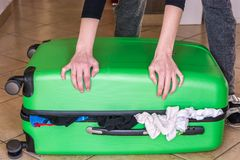 Woman tries to close overfilled suitcase stock image
