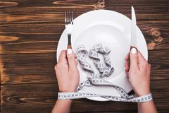 Hand with knife and fork. Woman tries to follow a diet. hand with knife and fork. top view of plate Stock Images