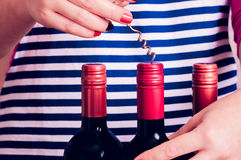 Woman tries to open a bottle of wine. Woman tries open a bottle of wine with a corkscrew Stock Photography