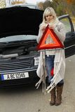 Woman tries to open an emergency sign. To warn other drivers Royalty Free Stock Photography