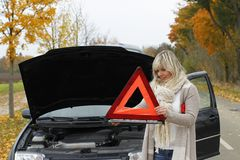 Woman tries to open an emergency sign. To warn other drivers stock images