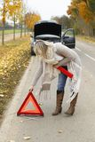 Woman tries to open an emergency sign. To warn other drivers stock photo