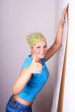 Woman tries on wall-papers to wall. Young woman tries on wall-papers to wall Royalty Free Stock Photo