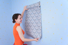Woman tries on wall-papers to wall. Young woman tries on wall-papers to wall Royalty Free Stock Images