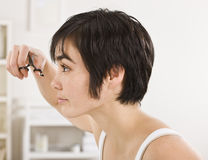 Woman Trimming Bangs. A woman is standing in front of the mirror and trimming her bangs. Vertically framed shot royalty free stock photos