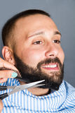 Woman is trimming the beard of a young man Stock Images
