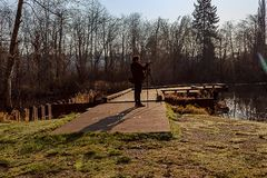 Woman with tripod and camera. Photographer on fishing dock shoots along winter lake Royalty Free Stock Image