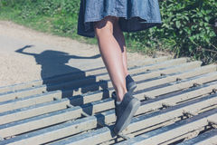 Woman tripping on cattle grid. A young woman is tripping on a cattle grid in the countryside Royalty Free Stock Image
