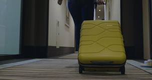 Woman with trolley bag looking for room in hotel stock video footage