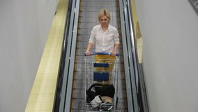 A woman with a trolley of products down the escalator in the supermarket stock video footage