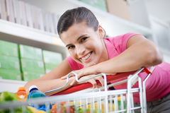 Woman with trolley at store Royalty Free Stock Image