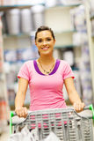 Woman trolley supermarket. Happy young woman pushing trolley in supermarket Stock Images