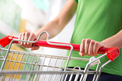 Woman with trolley at supermarket Stock Photo