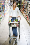 Woman with a trolley walking down a supermarket aisle Royalty Free Stock Photography