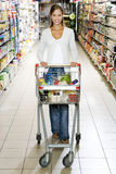 Woman with a trolley walking down a supermarket aisle Royalty Free Stock Photo