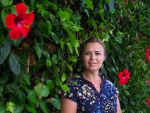 Woman. On tropical background with red flowers of hibiscus bush Royalty Free Stock Image