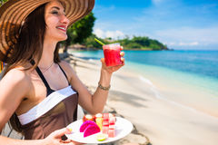 Woman at tropical beach eating fruit for breakfast Royalty Free Stock Photos