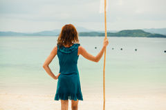 Woman on tropical beach with flag Royalty Free Stock Photography