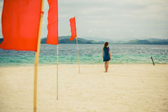 Woman on tropical beach with flags Royalty Free Stock Photography