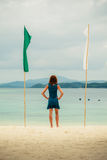 Woman on tropical beach with flags Royalty Free Stock Photo